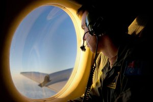 RAAF Airborne Electronics Analyst Sergeant Patrick Manser looks out of an observation window aboard an aircraft during the search for debris from the missing Malaysian Airlines flight MH370